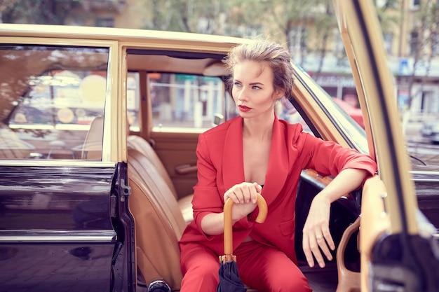 Mooie jonge vrouw, gekleed in rood kostuum, met paraplu zittend in retro auto