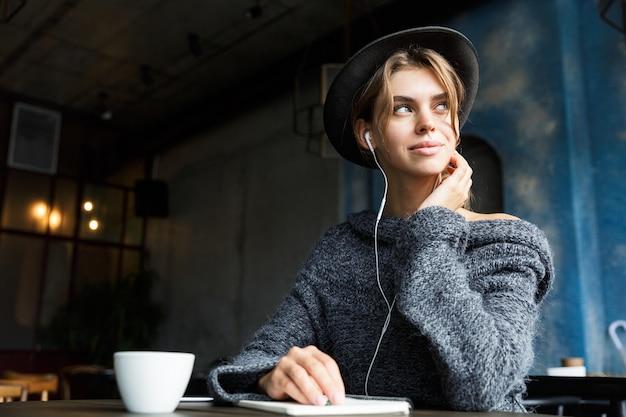 Mooie jonge vrouw gekleed in trui en hoed zit aan de café tafel binnenshuis, luisteren naar muziek met koptelefoon, koffie drinken, notities maken, wegkijken