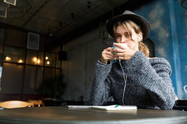 Mooie jonge vrouw gekleed in trui en hoed zit aan de café tafel binnenshuis, luisteren naar muziek met koptelefoon, koffie drinken