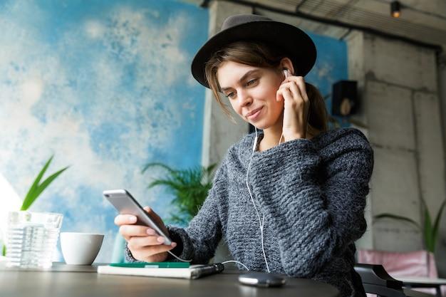 Mooie jonge vrouw gekleed in trui en hoed zittend in de stoel aan de café-tafel, luisteren naar muziek met koptelefoon, met behulp van mobiele telefoon, stijlvol interieur