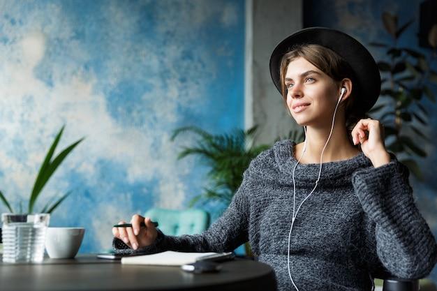 Mooie jonge vrouw gekleed in trui en hoed zittend in de stoel aan de café-tafel, luisteren naar muziek met koptelefoon, stijlvol interieur, notities maken