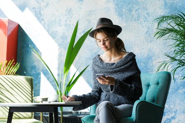 Mooie jonge vrouw gekleed in trui en hoed zittend in de stoel aan de cafétafel, met behulp van mobiele telefoon, notities maken, stijlvol interieur
