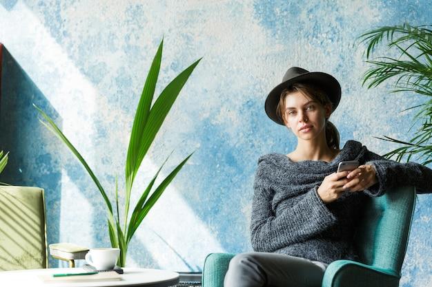 Mooie jonge vrouw gekleed in trui en hoed zittend in de stoel aan de cafétafel, met mobiele telefoon, stijlvol interieur