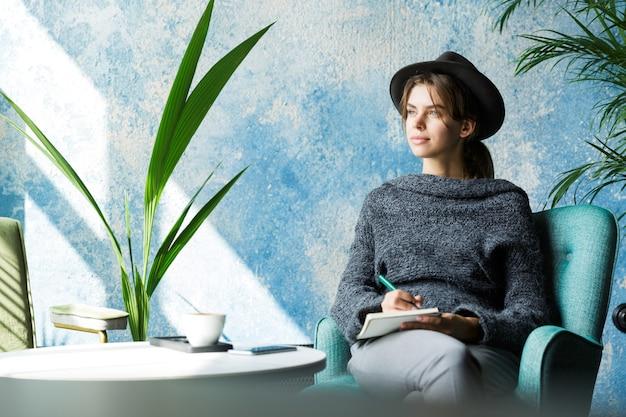 Mooie jonge vrouw gekleed in trui en hoed zittend in een stoel aan de cafétafel, notities maken