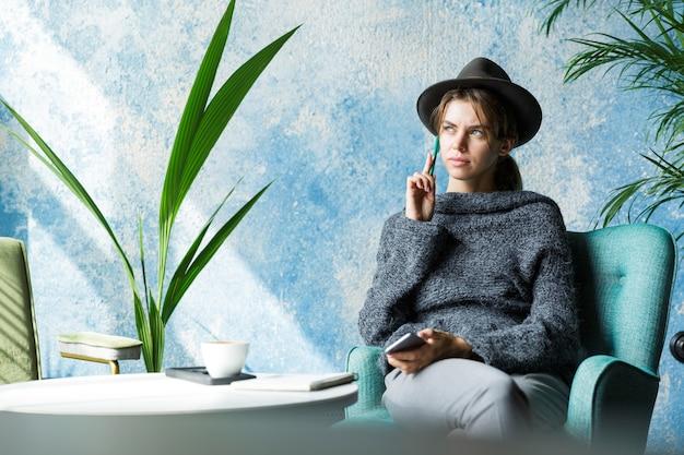 Mooie jonge vrouw gekleed in trui en hoed zittend in een stoel aan de cafétafel, praten op mobiele telefoon, stijlvol interieur