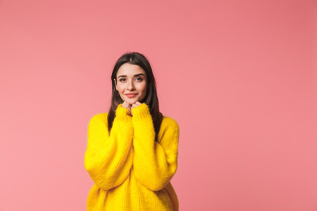 Mooie jonge vrouw, gekleed in warme trui staande geïsoleerd over roze, poseren