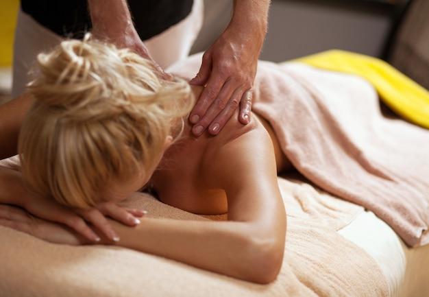 Mooie jonge vrouw geniet van massage