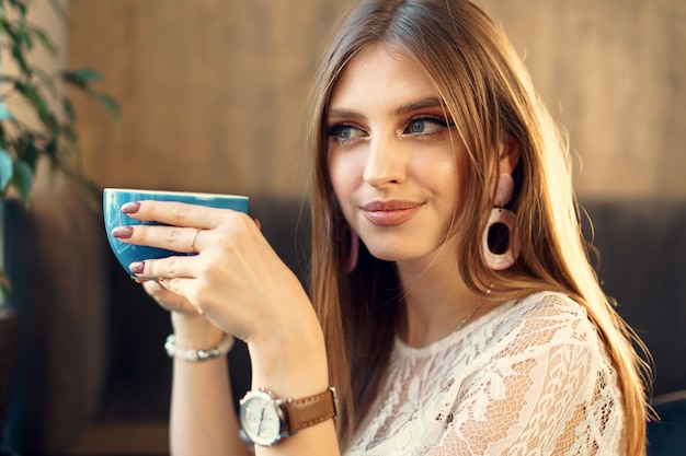 Mooie jonge vrouw genieten van een kopje koffie in een koffieshop