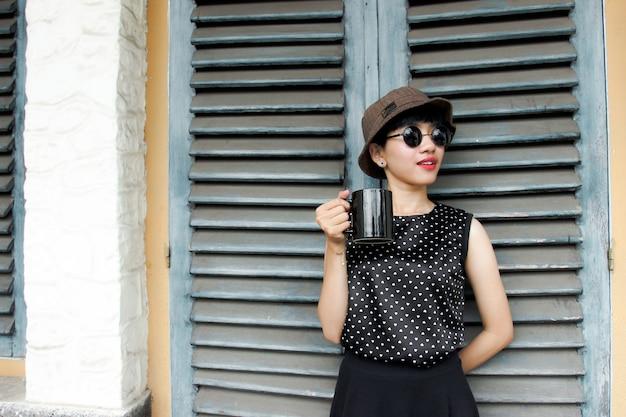 Mooie jonge vrouw genietend van koffie voor haar deur
