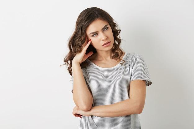 Mooie jonge vrouw, gestrest, denken over probleem, hipster stijl, gekleed in t-shirt, geïsoleerd op een witte achtergrond,