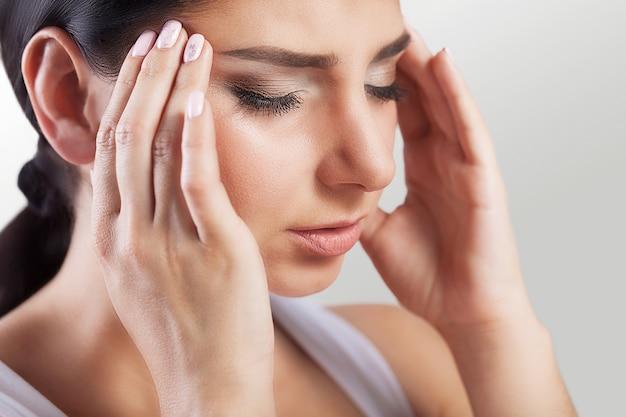 Mooie jonge vrouw gevoel sterke hoofdpijn