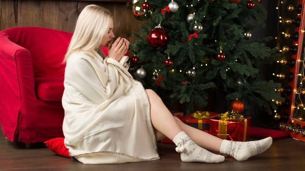 Mooie jonge vrouw gewikkeld in een plaid zit in een rode stoel met een kopje thee of koffie in het interieur van het nieuwe jaar in de buurt van de kerstboom. - afbeelding