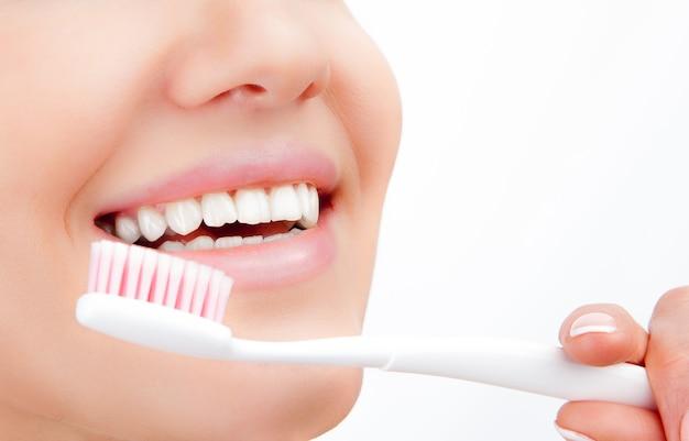 Mooie jonge vrouw glimlach met tanden poetsen. tandheelkundige gezondheid achtergrond.