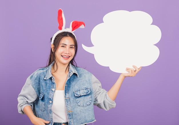 Mooie jonge vrouw glimlachend opgewonden dragend konijnenoren en jeans met lege tekstballon