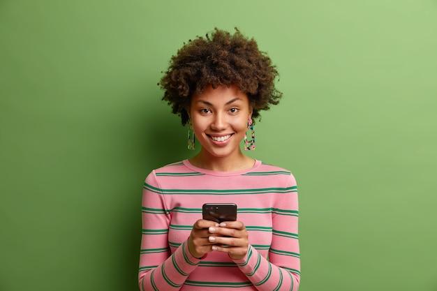 Mooie jonge vrouw glimlacht positief stuurt sms-berichten via smartphone geniet van online communicatie altijd in contact draagt gestreepte trui geïsoleerd over groene muur