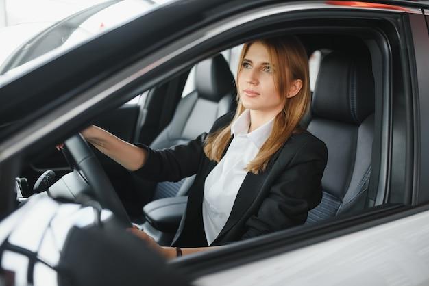 Mooie jonge vrouw haar nieuwe auto rijden (kleur getinte afbeelding; ondiepe dof)