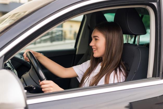Mooie jonge vrouw haar nieuwe auto rijden op de weg