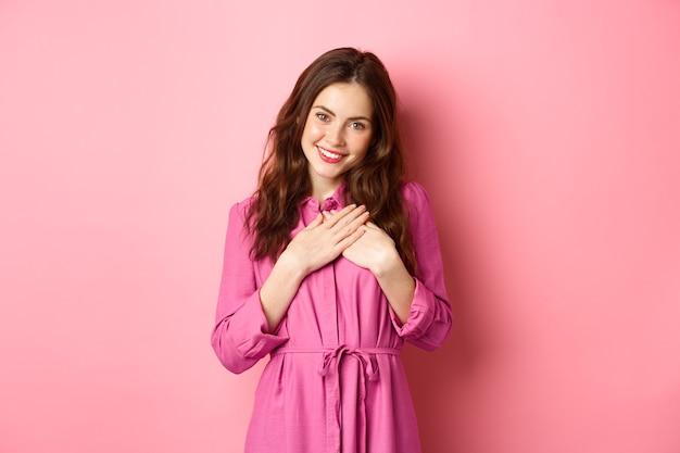 Mooie jonge vrouw hand in hand op het hart en dankbaar glimlachend, dankbaarheid uiten, bedanken, hartverwarmend geschenk ontvangen, staande over roze muur.