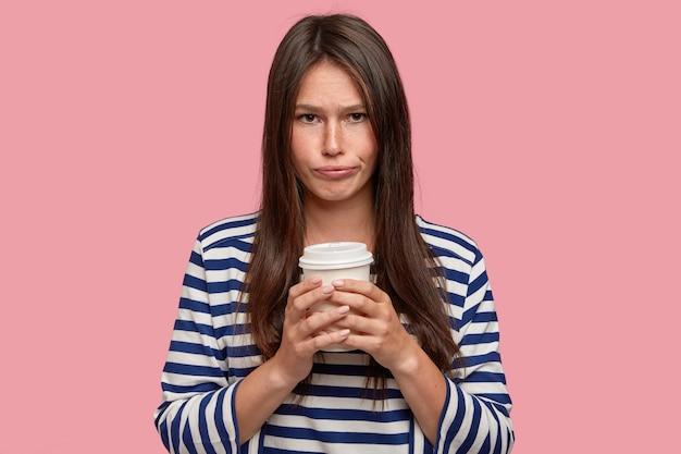Mooie jonge vrouw heeft een droevige, ellendige uitdrukking, houdt papieren wegwerpbeker vast, drinkt koffie, voelt zich boos