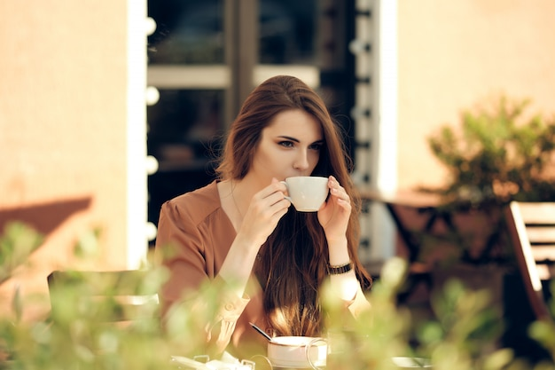 Mooie jonge vrouw heeft koffiepauze in het midden van zonnige dag