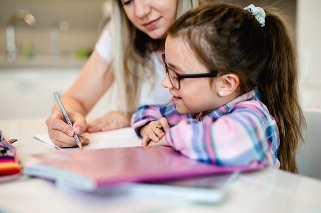 Mooie jonge vrouw helpt haar jongere zus met huiswerk