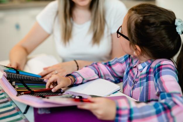 Mooie jonge vrouw helpt haar jongere zus met huiswerk.