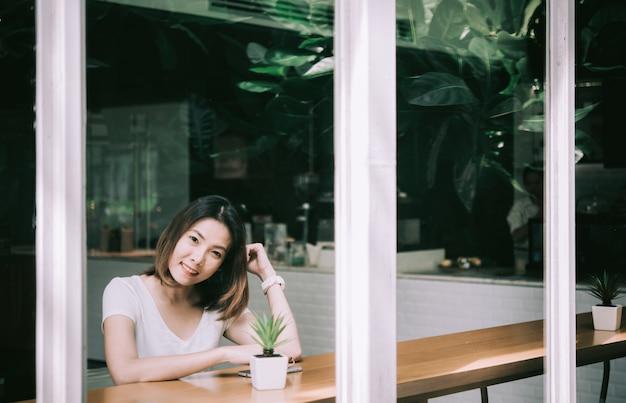 Mooie jonge vrouw het drinken koffiezitting door het venster in de koffie.