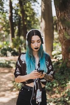Mooie jonge vrouw het luisteren muziek op hoofdtelefoon door celtelefoon