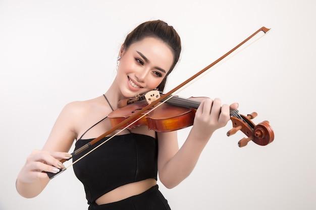 Mooie jonge vrouw het spelen viool over witte achtergrond