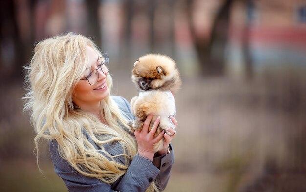 Mooie jonge vrouw houdt een puppy in haar armen. liefde voor huisdieren en emoties.