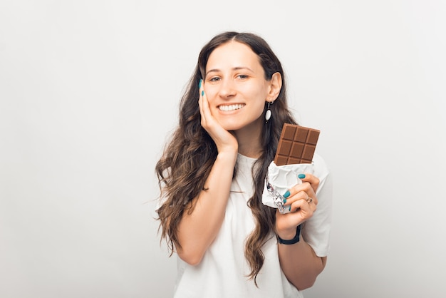 Mooie jonge vrouw houdt een reep chocolade vast en lacht naar de camera.
