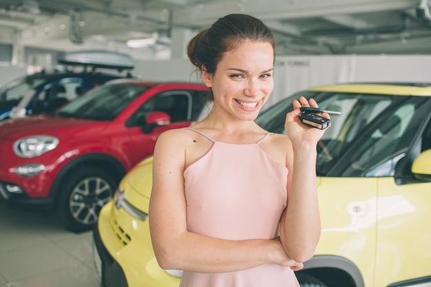 Mooie jonge vrouw houdt een sleutel in autodealer. autozaken, autoverkoop, - gelukkig vrouwelijk model in autoshow of salon.