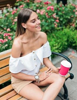 Mooie jonge vrouw houdt kopje koffie zittend op een bankje in het park