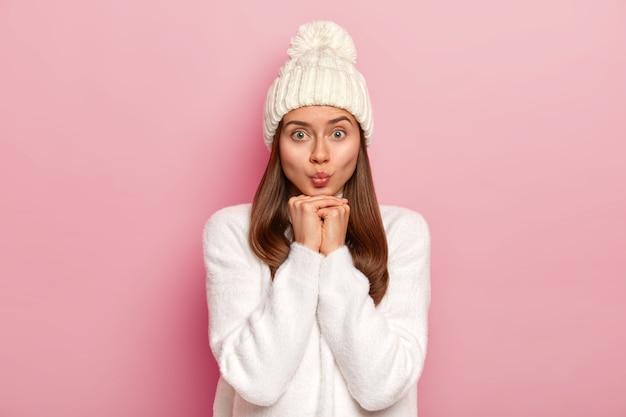 Mooie jonge vrouw houdt lippen gevouwen, handen onder de kin, kijkt aantrekkelijk in de camera, draagt witte winteroutfit, heeft een gezonde huid, goed verzorgde teint, geïsoleerd over een roze muur. gezichtsuitdrukkingen