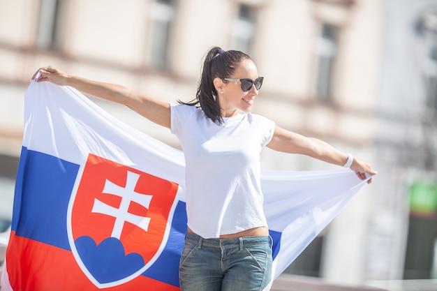 Mooie jonge vrouw houdt op een zonnige dag een vlag van slowakije vast en draagt een zonnebril.
