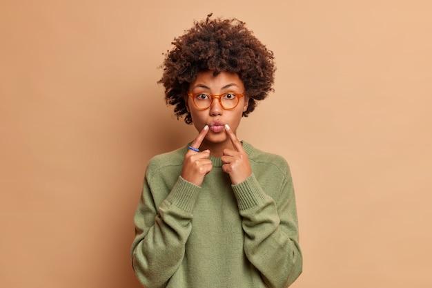 Mooie jonge vrouw houdt wijsvingers in de buurt van gevouwen lippen maakt gezicht aan voorkant wil kussen iemand draagt bril en trui geïsoleerd over bruine muur