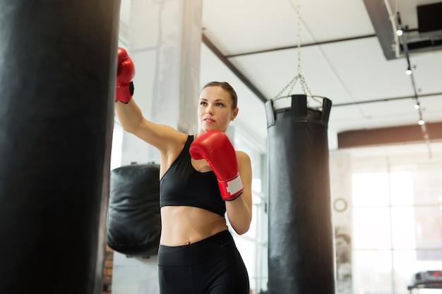 Mooie jonge vrouw houdt zich bezig met boksen met een bokszak in de sportschool