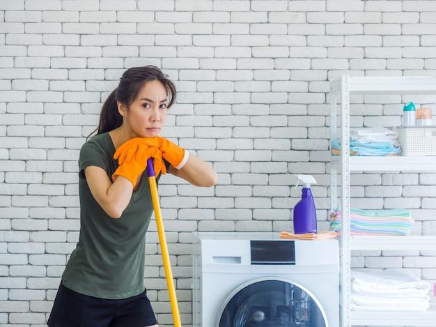 Mooie jonge vrouw, huisvrouw oranje beschermende rubberen handschoenen met ongelukkig en moe gezicht dragen na het schoonmaken met dweil in de buurt van wasmachine in witte kamer.