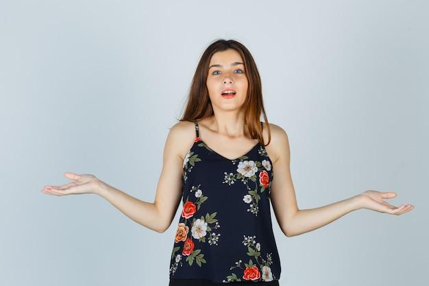 Mooie jonge vrouw hulpeloos gebaar in blouse tonen en verbaasd kijken