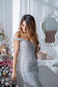Mooie jonge vrouw in avondjurk in de buurt van de kerstboom. vrolijk kerstfeest