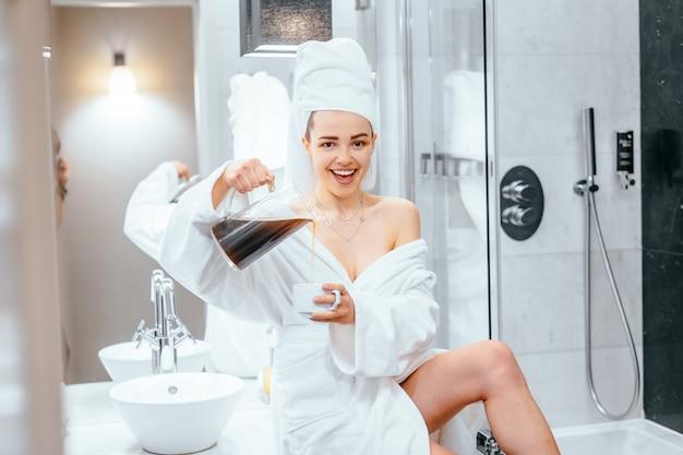 Mooie jonge vrouw in badjas en handdoek op haar hoofd zittend op een badkuip