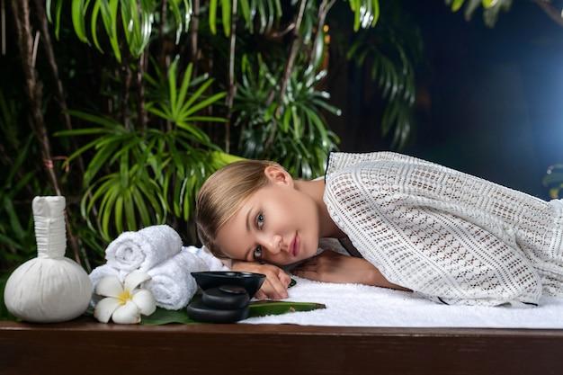 Mooie jonge vrouw in badjas het ontspannen op een lijst die op een massage wacht. spa en verzorging