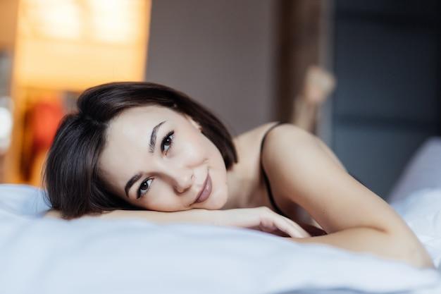 Mooie jonge vrouw in bed in de vroege ochtend