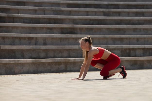 Mooie jonge vrouw in beginpositie in stadion in de zomer