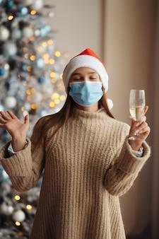 Mooie jonge vrouw in beschermend masker met glas champagne thuis.