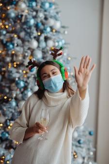 Mooie jonge vrouw in beschermend masker met glas champagne thuis
