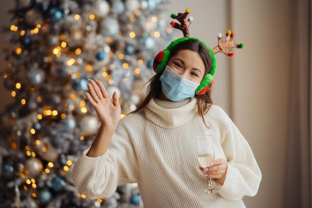 Mooie jonge vrouw in beschermend masker met glas champagne