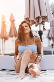 Mooie jonge vrouw in bikini die buiten bij het zwembad rust