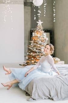 Mooie jonge vrouw in blauw witte jurk zittend op het bed