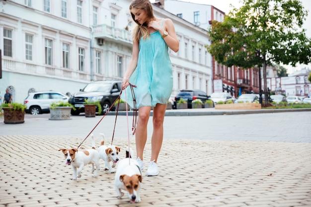 Mooie jonge vrouw in blauwe jurk die haar honden meeneemt voor een wandeling op straat